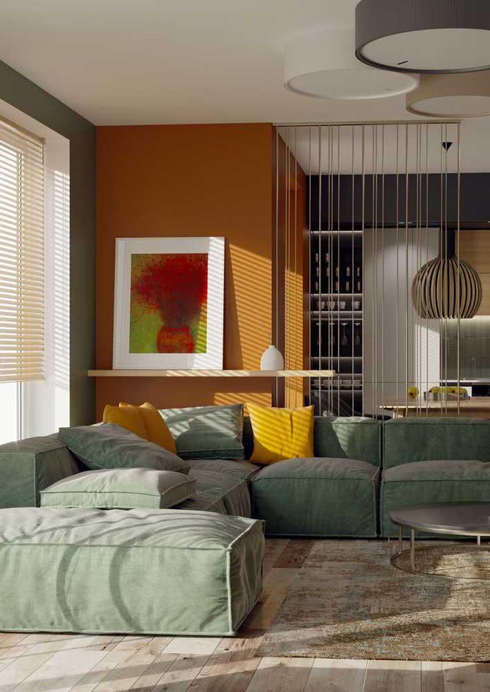 As linhas retas trazem um toque moderno ao sofá, enquanto o verde traz calma e aconchego para a sala