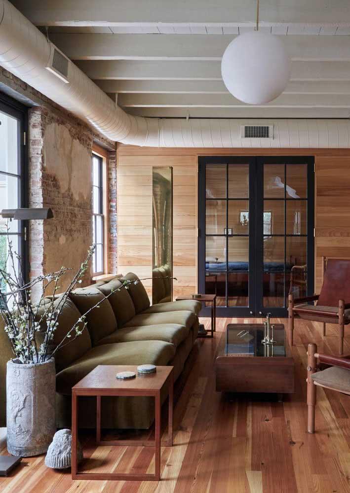 Sala rústica de madeira decorada com sofá verde