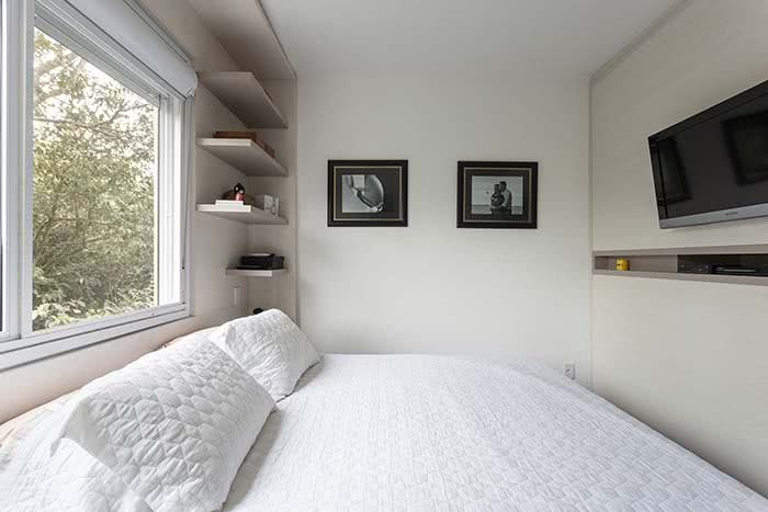 Cama grande em um quarto de casal bem apertadinho