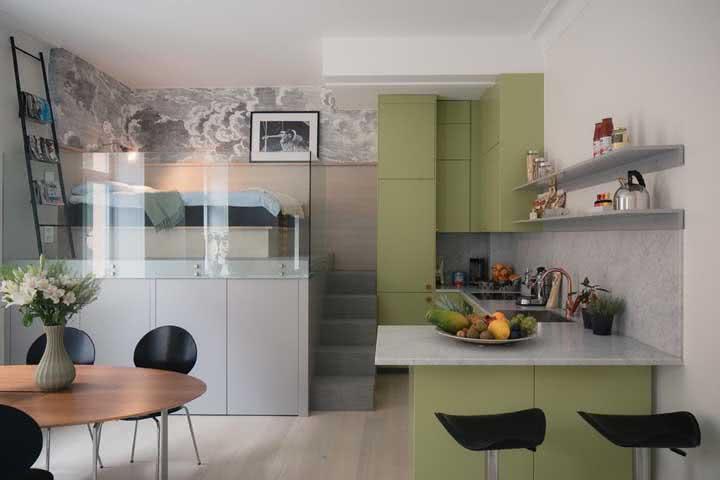 Casa pequena com guarda-corpo de vidro delimitando o espaço do quarto e da cozinha