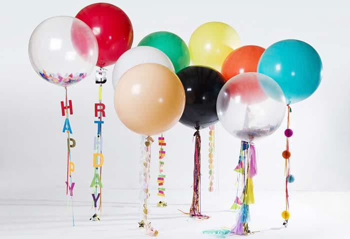 Balões coloridos suspensos com elementos decorativos
