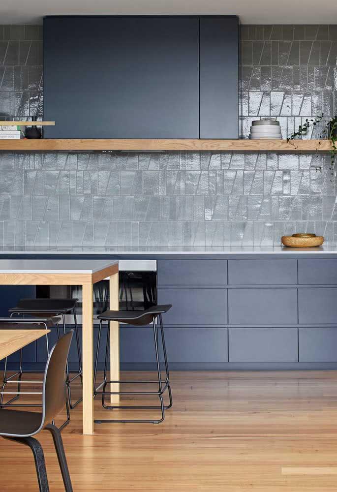 A pastilha da parede combina com a tonalidade dos armários formando um ambiente discreto e moderno