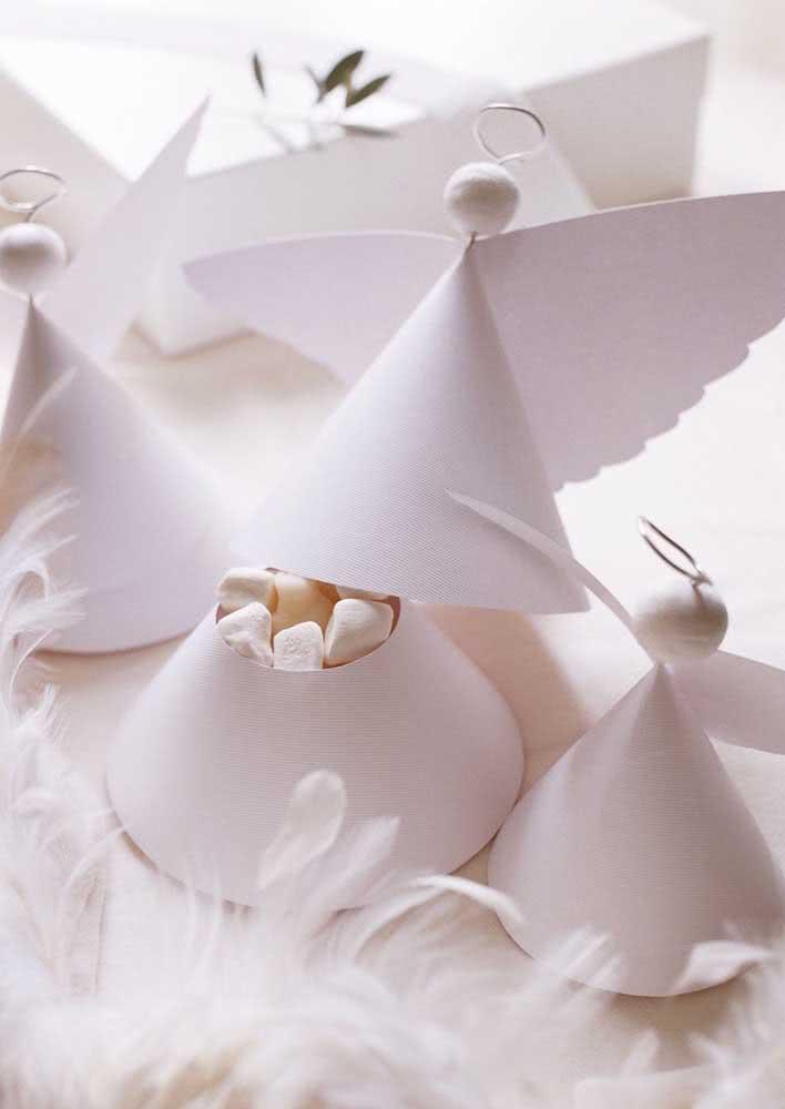 Mesa decorada com anjos de papel que servem como tampa para doces