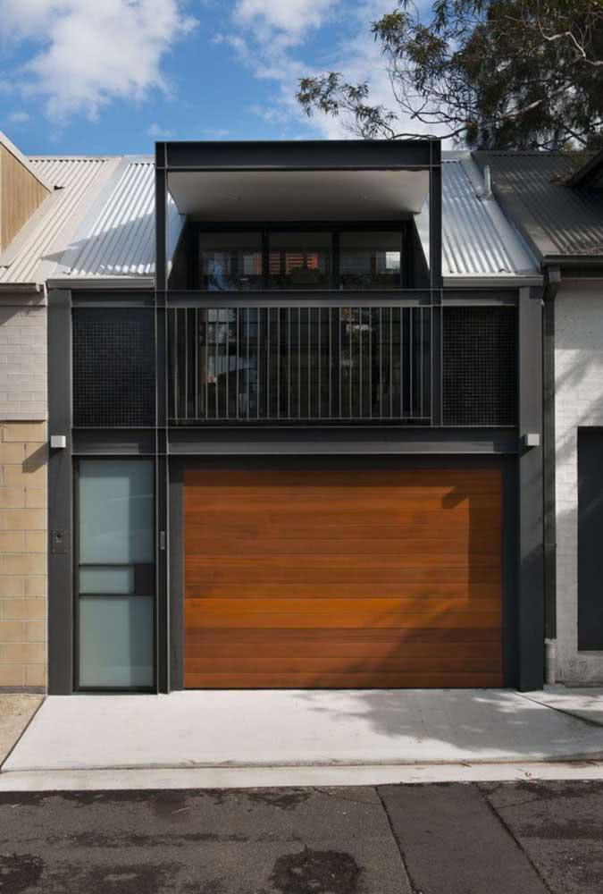 Estrutura metálica e elementos na cor preta em combinação com um belo portão de madeira.