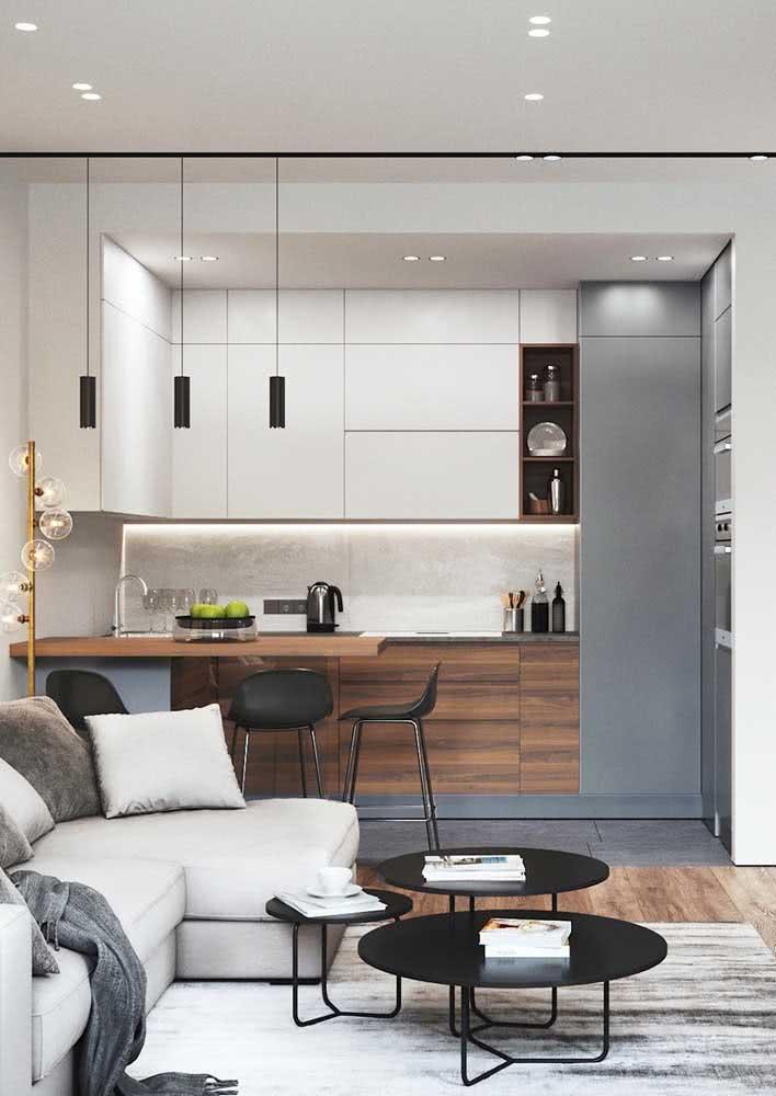 Cozinha americana simples e moderna com poucos elementos visíveis e armários sem puxadores.