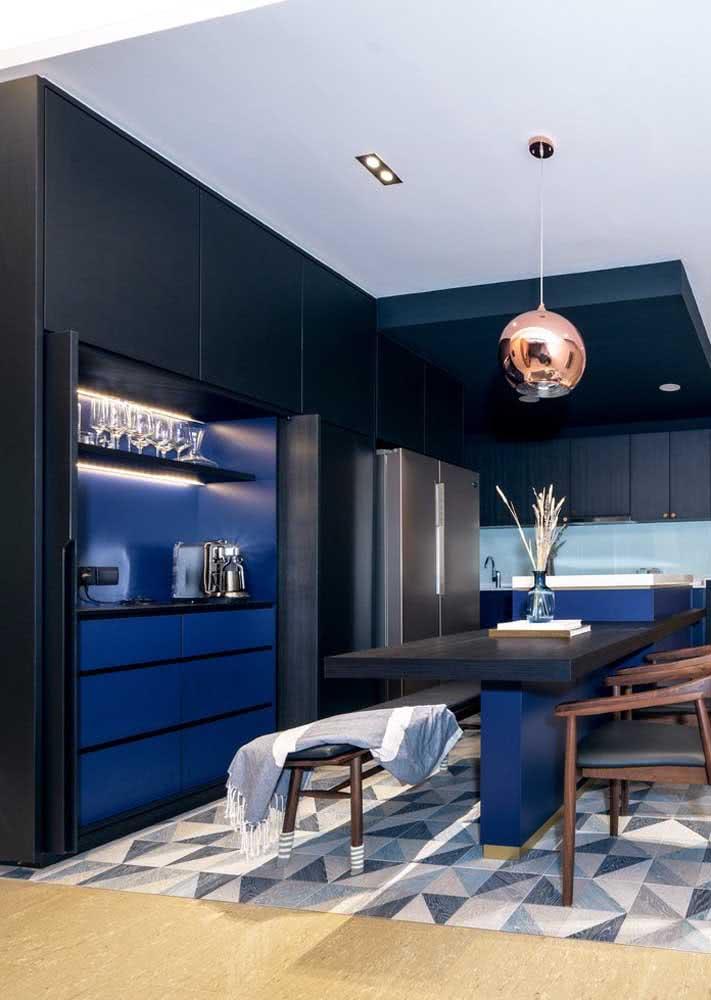 Cozinha planejada azul marinho com bancada central e piso com desenhos geométricos
