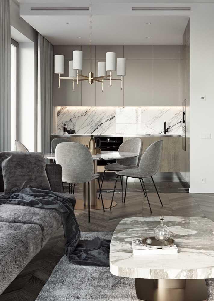 Cozinha com mesa de jantar redonda integrada e um belíssimo lustre pendente
