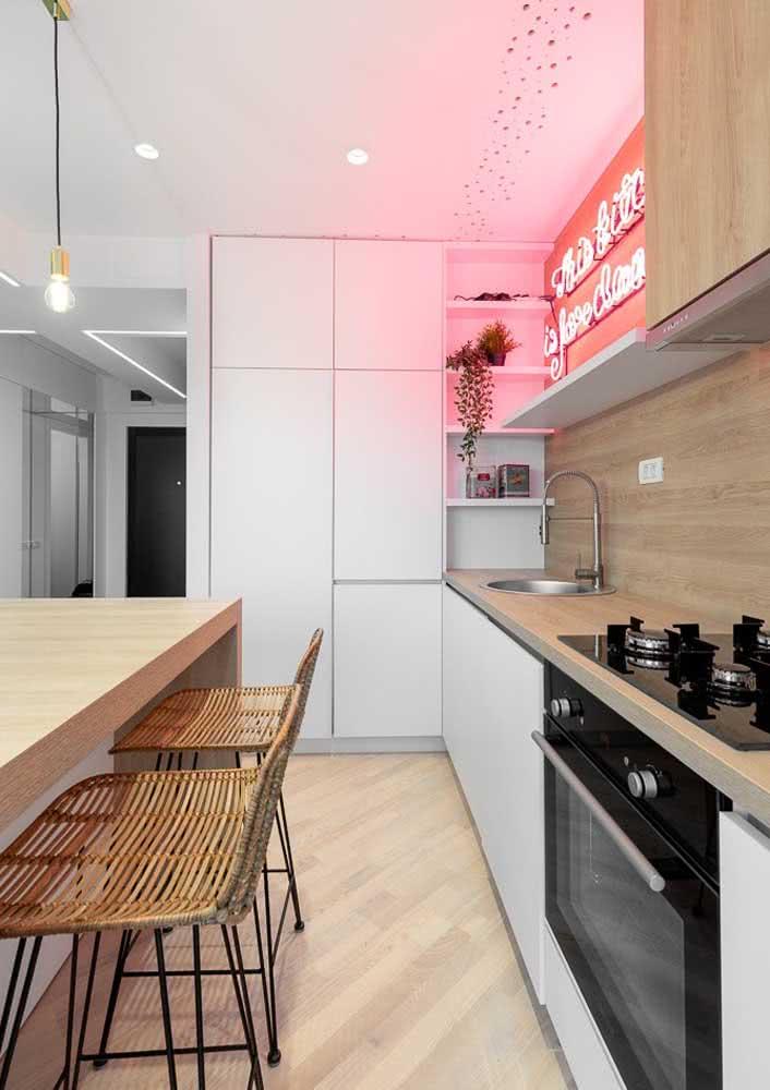 Cozinha planejada simples com bancada de madeira, armários brancos, ilha central com spots de iluminação e letreiro neon.