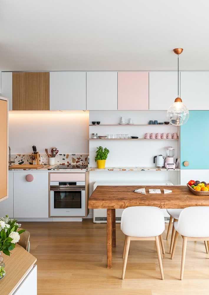 Cozinha candy color com pedra granilite na bancada e utensílios que acompanham as cores escolhidas no projeto.
