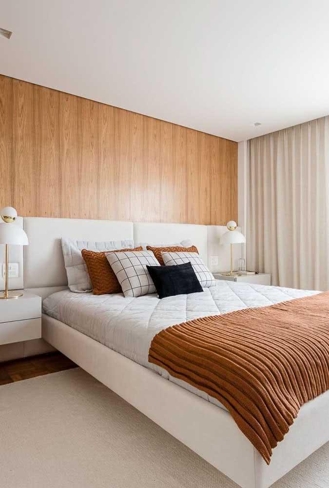 Aqui, o tom de caramelo da cama conversa diretamente com o painel de madeira
