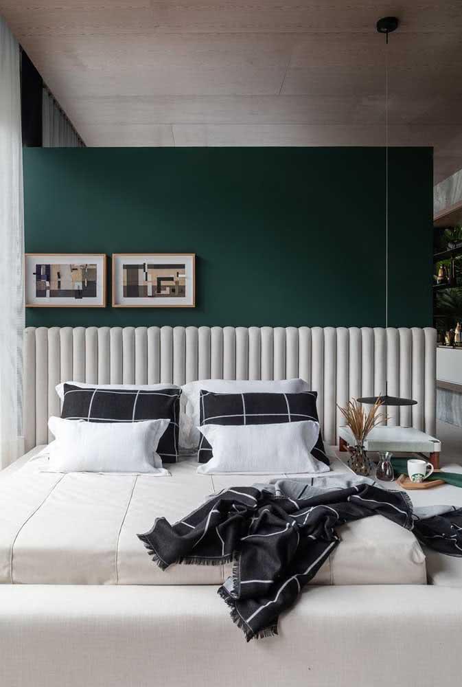 A parede verde forma uma linda composição com a cama em branco e preto