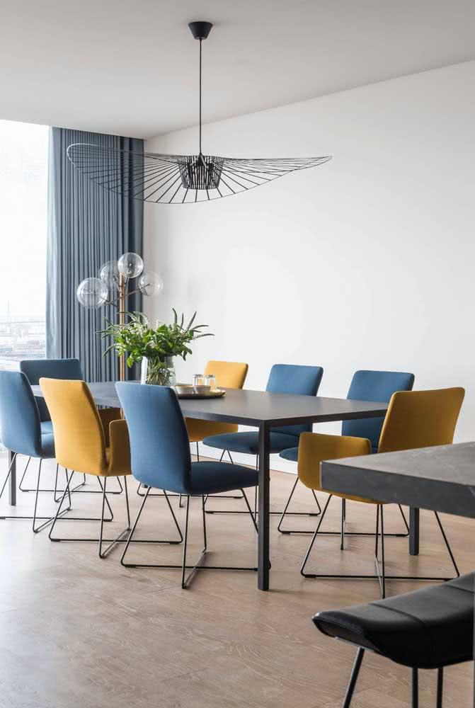 O destaque aqui vai para o tom fechado de amarelo das cadeiras combinado as demais cadeiras em azul escuro