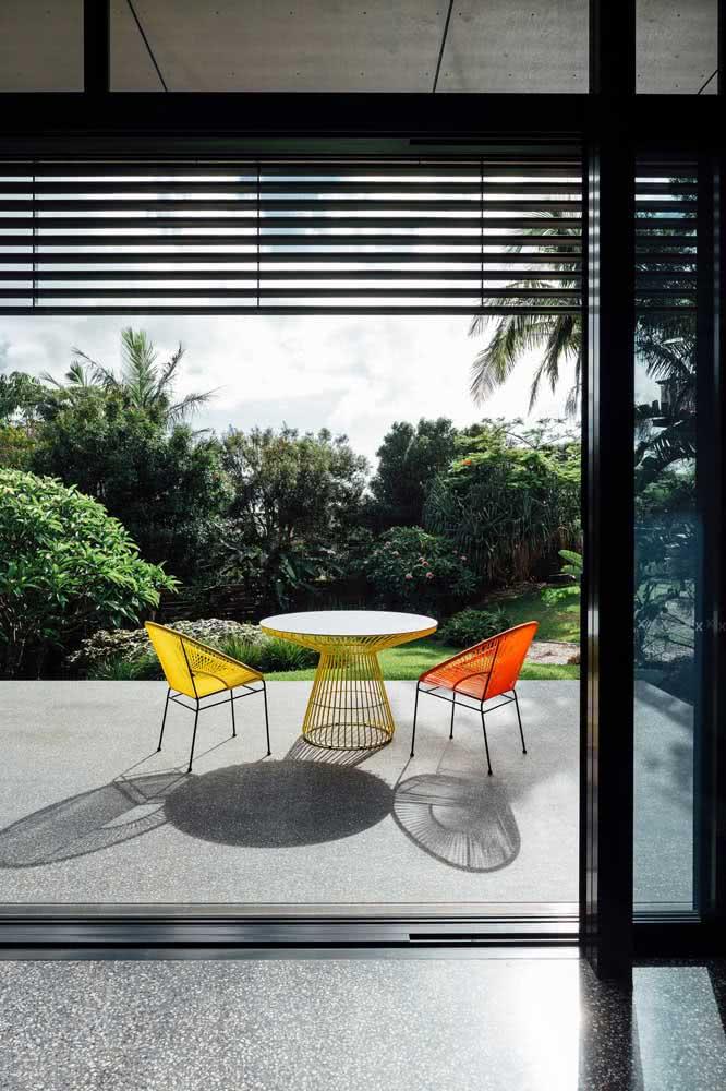 Uma releitura moderna da cadeira Acapulco em tons de amarelo e laranja para a varanda do quarto.