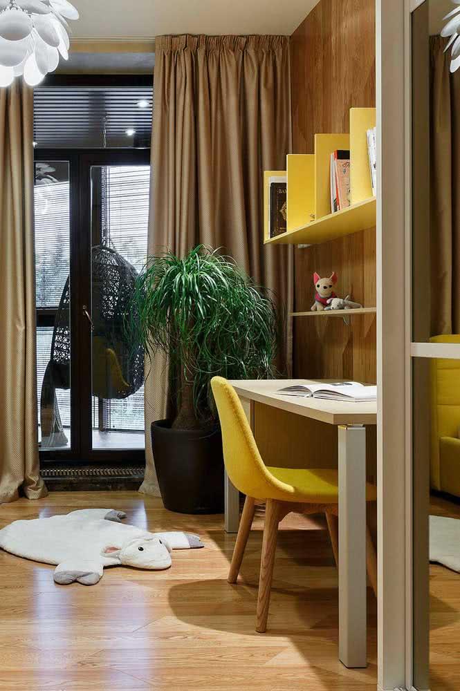 Cadeira amarela combinando com o restante da decoração. Repare na combinação harmônica entre o amarelo e os tons de madeira