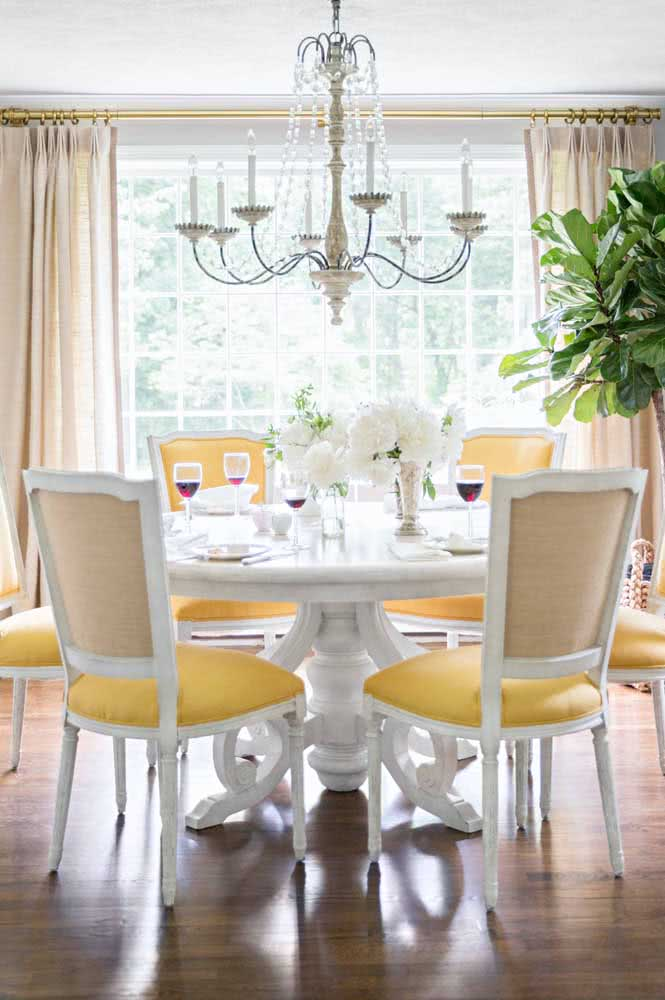 As clássicas cadeiras de madeira branca com estofado amarelo