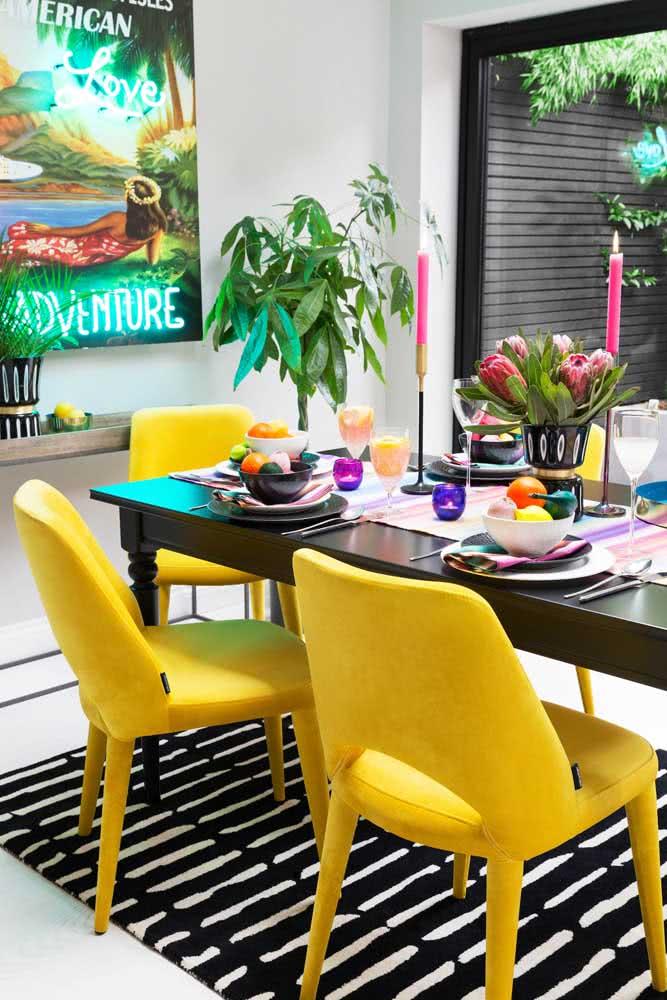 O destaque dessa sala de jantar é o contraste entre o tapete preto e branco com as cadeiras amarelas