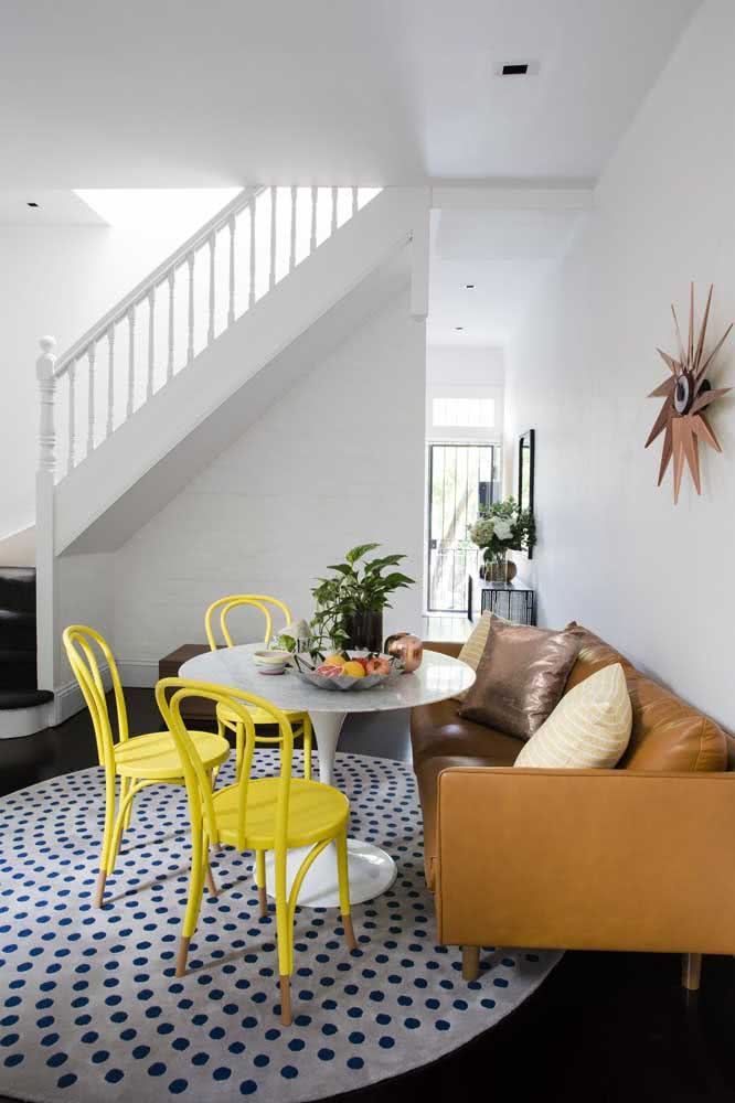 Sala de estar com mesa ao estilo canto alemão rodeada pelas cadeiras amarelas