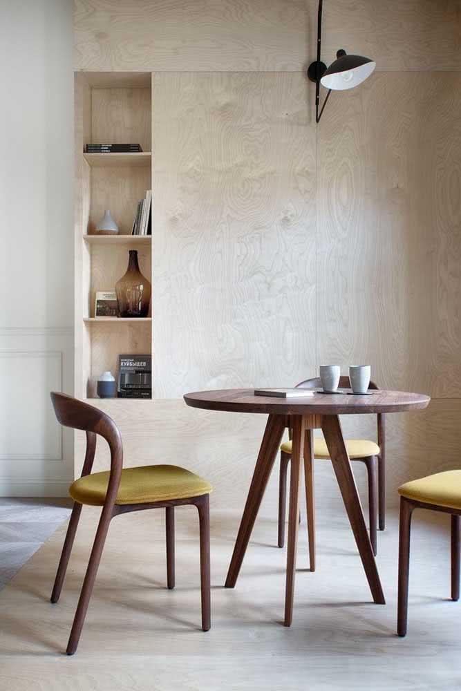 Aqui, o tom amarelo queimado do estofado das cadeiras de madeira se harmoniza perfeitamente com o ambiente de estilo natural