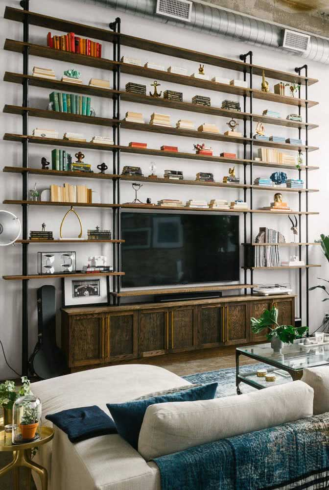 Prateleiras industriais no lugar da estante. Aqui, o estilo decorativo é complementado pela tubulação de ar e pela parede de cimento queimado