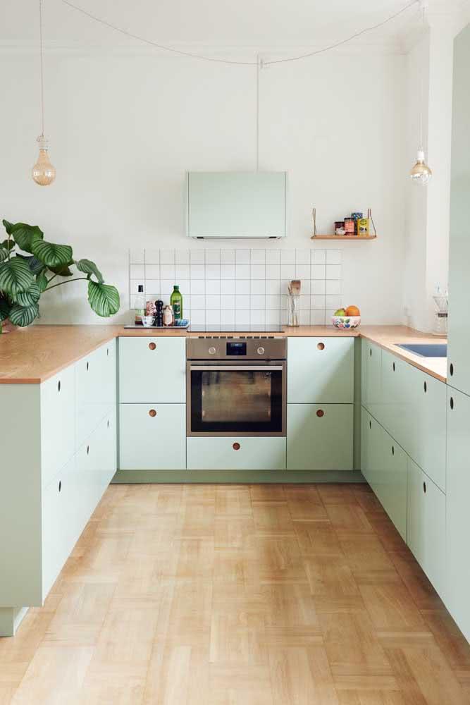 Cozinha em U com armários verde menta. A área de armazenamento ficou apenas na parte de baixo