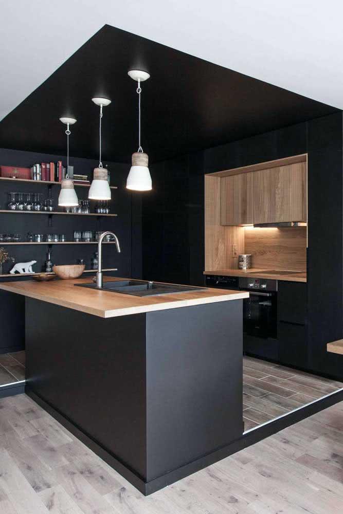 Uma cozinha em U envolvida pela pintura preta que delimita o ambiente do restante da casa
