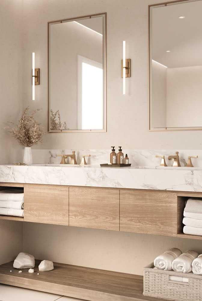 No banheiro, a cor pérola pode ser usada junto de uma bancada de mármore branco e móveis amadeirados
