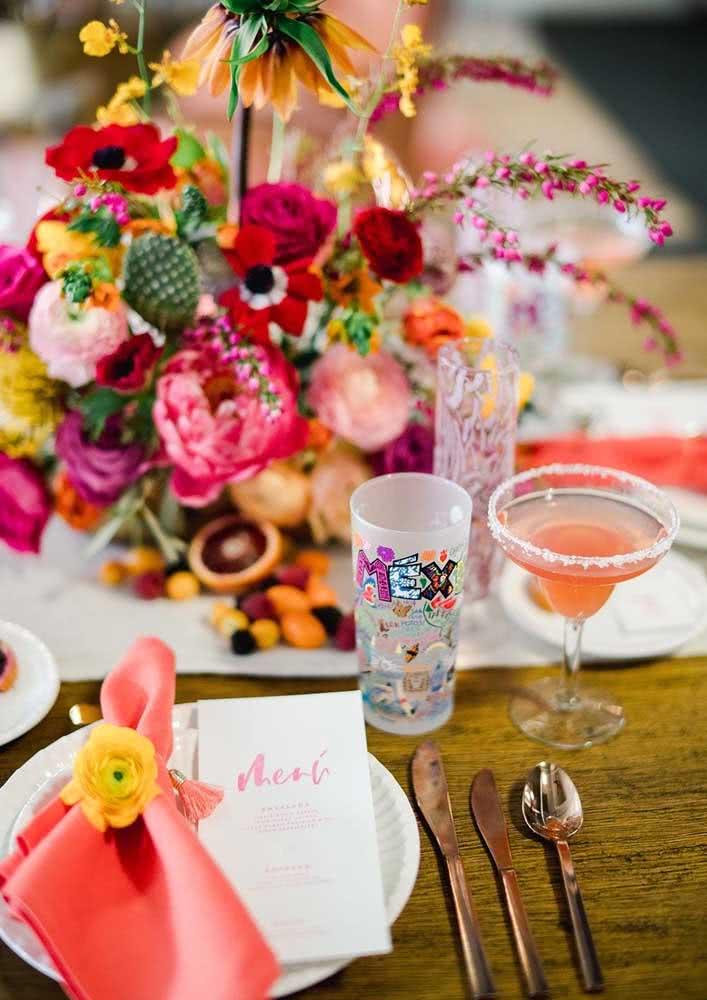 A mesa posta traz menu individual e um lenço delicadamente envolvido pela flor