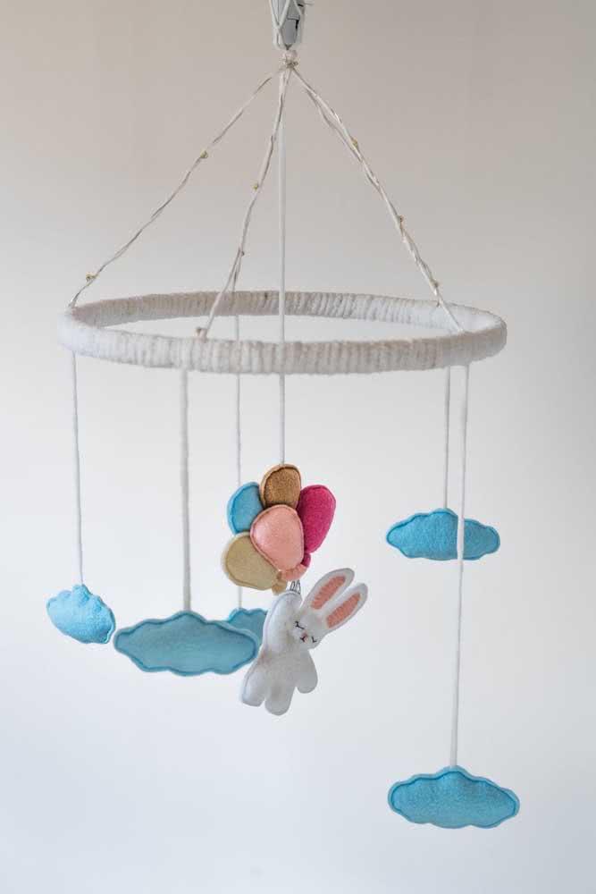 Móbile com nuvens de feltro azuis e um coelhinho charmoso pendurado