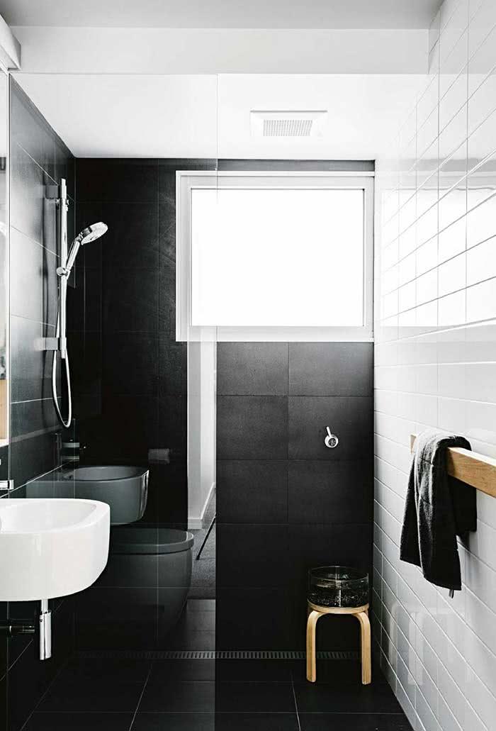 Iluminação ampla neste banheiro com piso e revestimento de parede na cor preta e branca