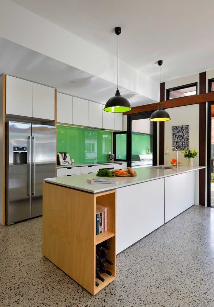 Cozinha com verde aplicado na parede da bancada e nas luminárias. Outra forma de acrescentar a cor no ambiente é utilizando vasos e plantas.