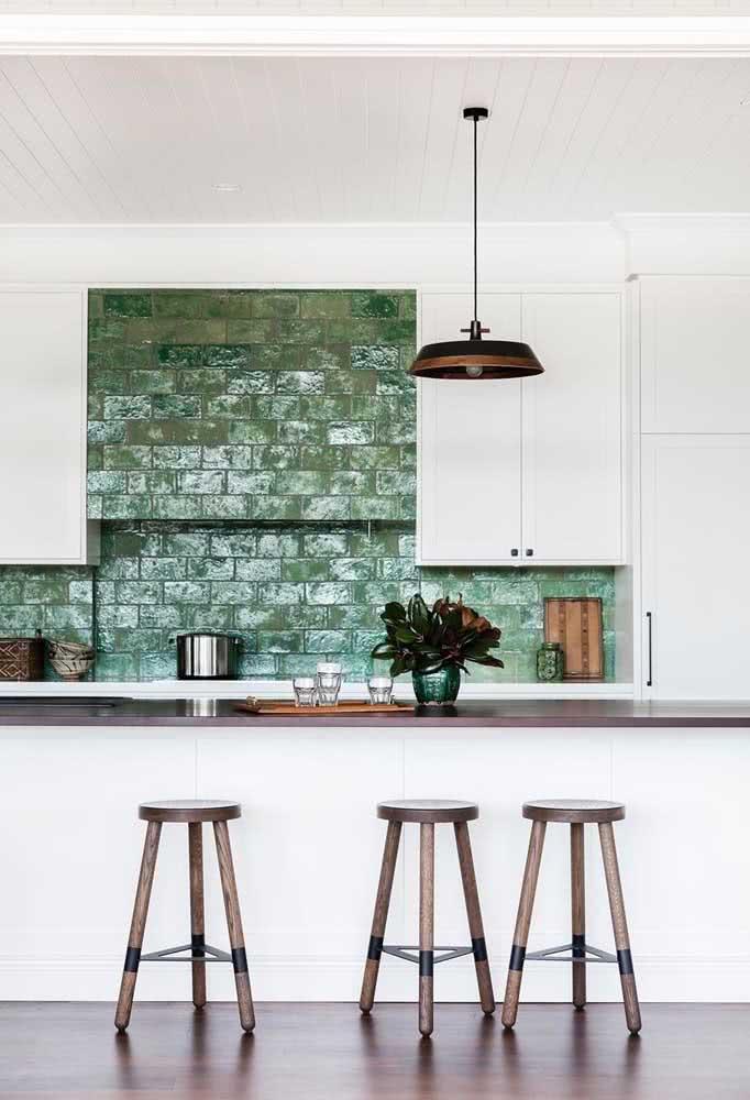 Cozinha americana com parede verde entre a bancada e os armários.