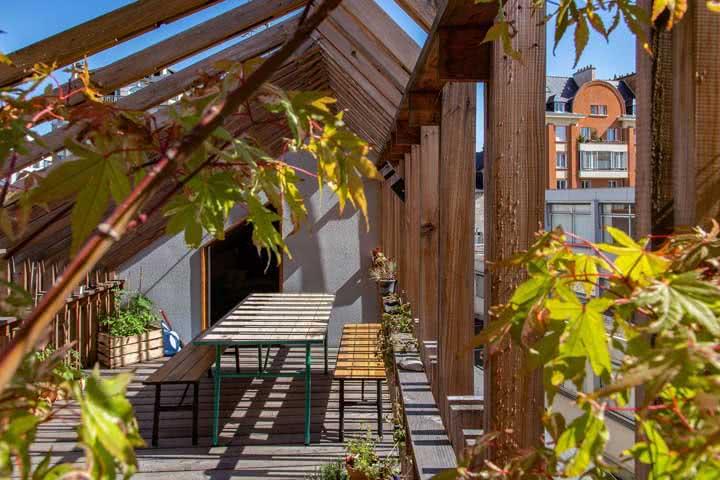 Pergolado de madeira que acompanha o desenho da residência