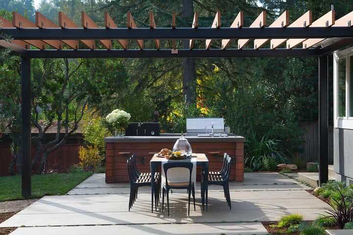 Área gourmet com churrasqueira com proteção do pergolado para a mesa de refeições.