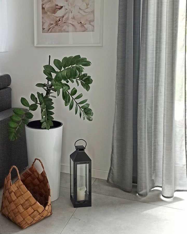Aqui o vaso com a planta foi posicionado atrás do sofá junto com outros objetos decorativos