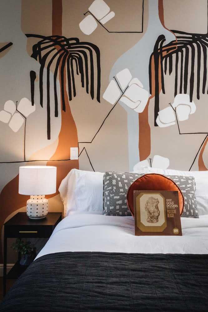Pintura abstrata na parede da cabeceira da cama com branco, bege, preto e tom terroso.