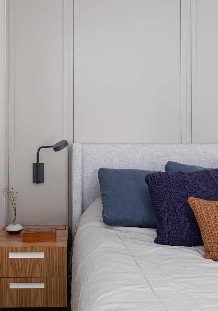 Aqui as almofadas trazem cor ao ambiente do quarto de casal.