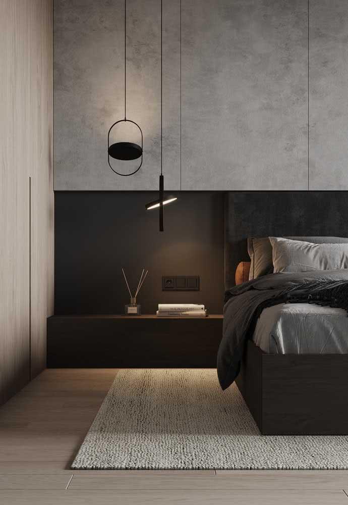 Tons de cinza na parede e preto na cabeceira e na base da cama de casal.