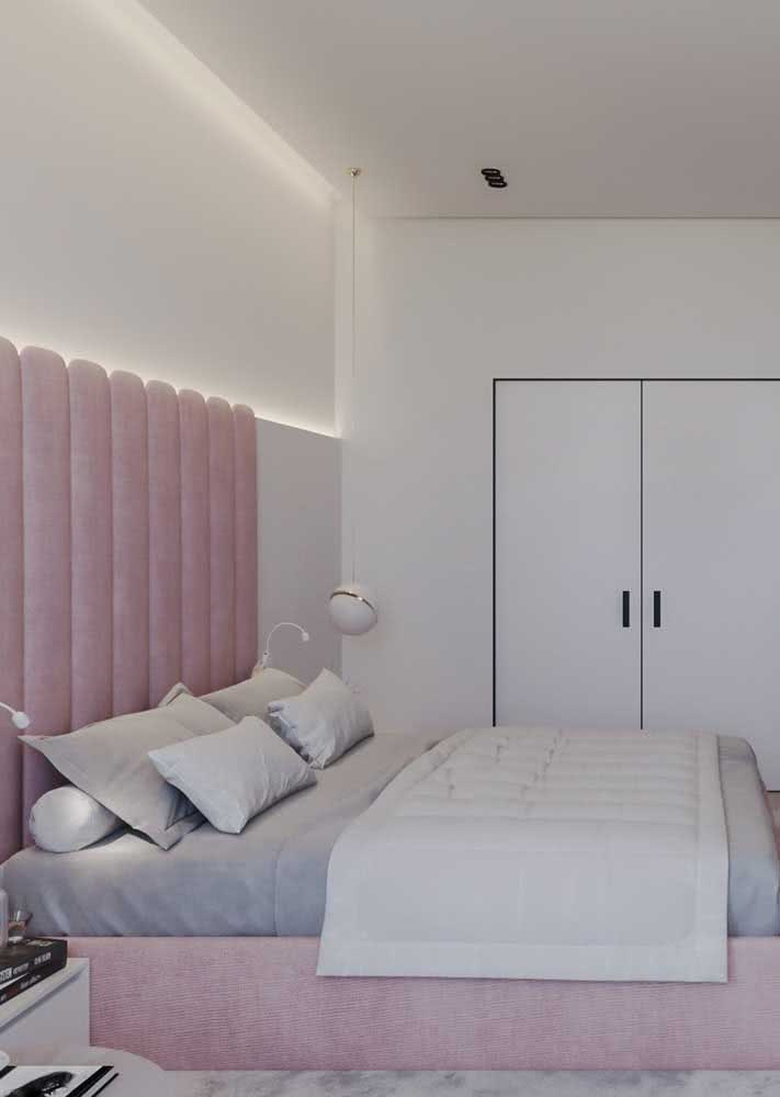 Em um quarto branco, a cabeceira e a base da cama tem a cor rosa.