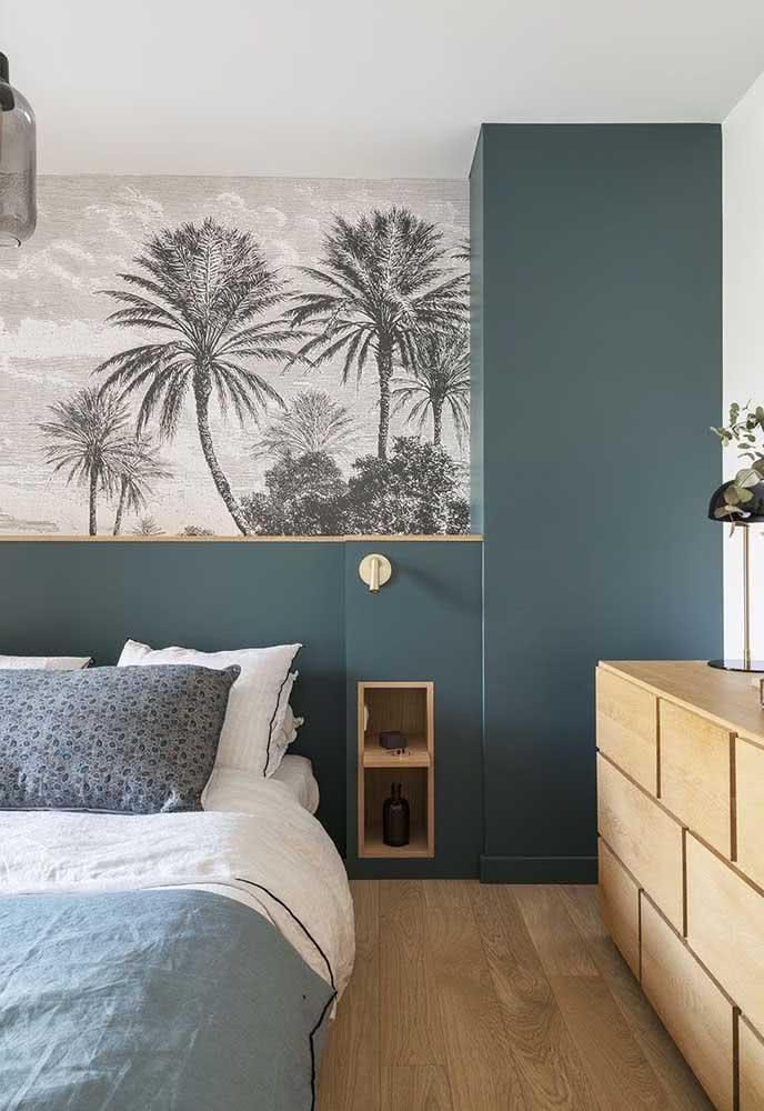 Quarto com o duo de branco azul petróleo na pintura da parede da cabeceira. Detalhe para o papel de parede com ilustrações de coqueiros.