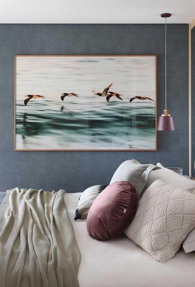 Lustre pendente, quadro e pintura da parede como protagonistas das cores do quarto.