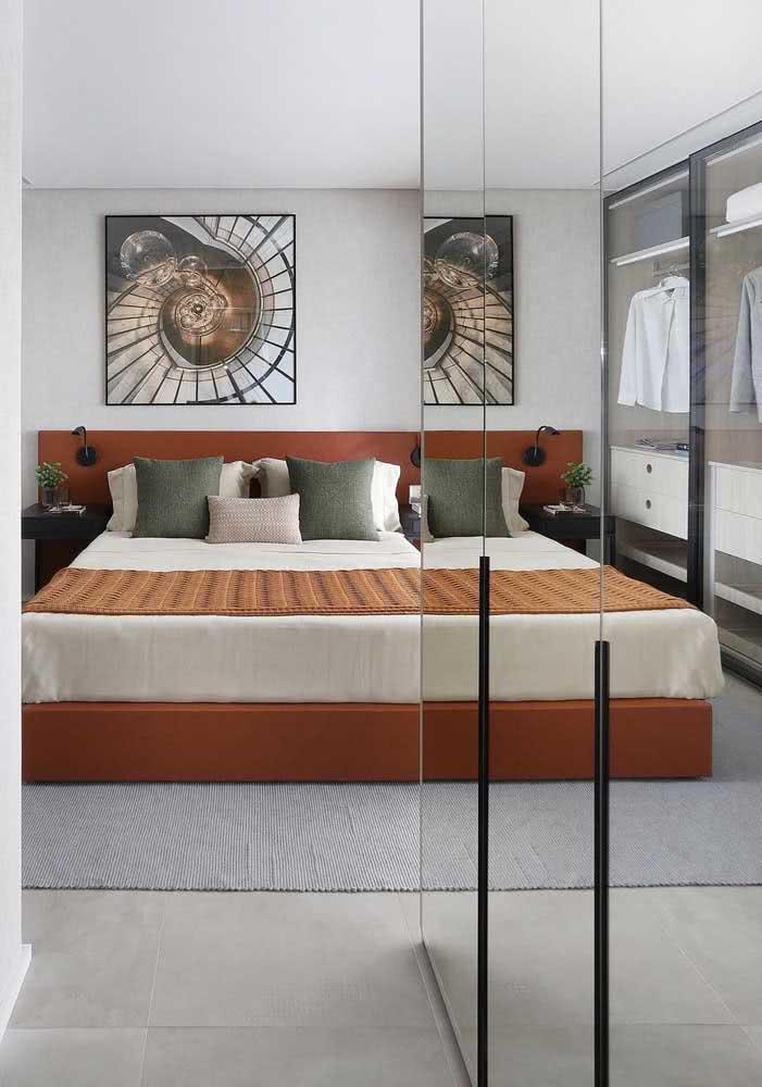 Quarto com parede cinza, tom terroso na cabeceira de na base da cama box e almofadas verde musgo.