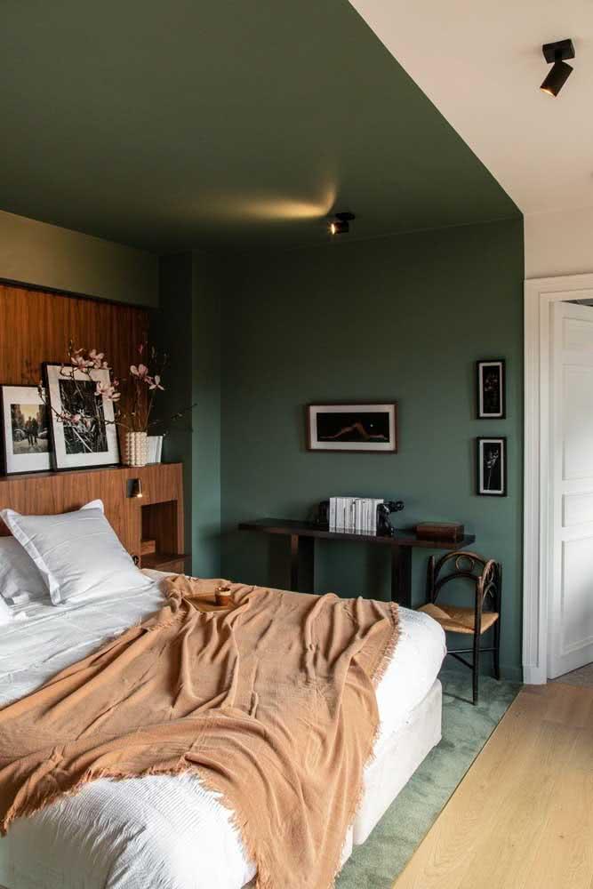 Quarto de casal com meia parede verde escura e a outra metade na cor branca. A pintura acompanha a parede e o teto do ambiente.
