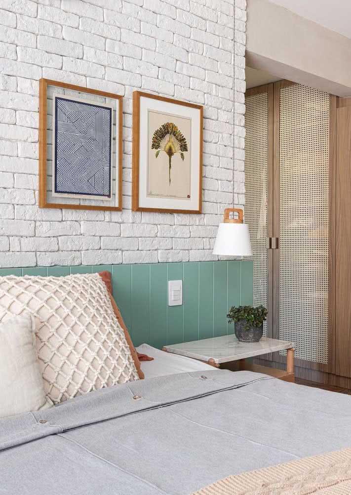 Cabeceira verde água e tijolinhos pintados de branco neste quarto com cama de casal.