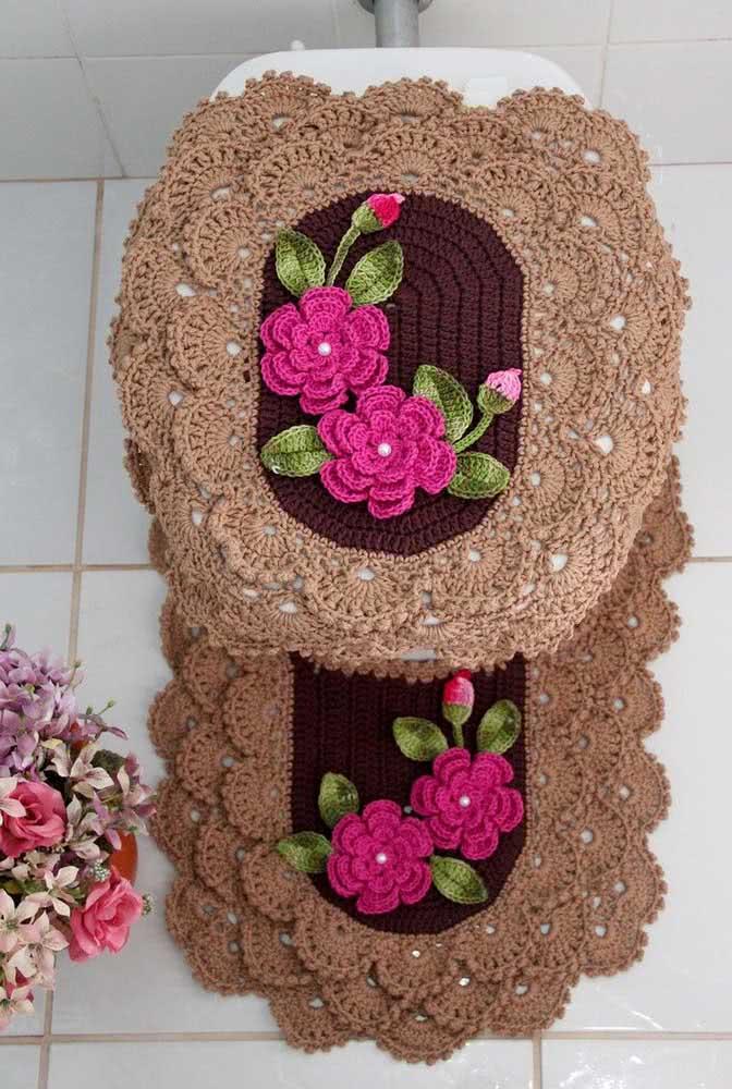 Decoração de jogo de banheiro de crochê com barbante marrom claro nas bordas e marrom escuro no centro. Detalhe para a bela flor rosa de crochê!