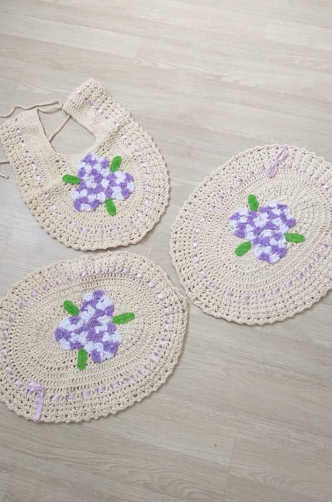 Jogo de banheiro de crochê com barbante cru e detalhes na cor roxa: uma solução delicada para a sua decoração.