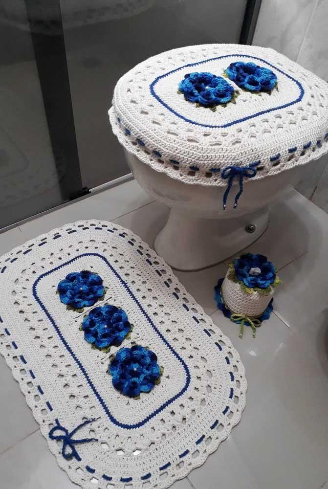 Flores azuis: já este conjunto de jogo de banheiro, capa de assento e porta papel higiênico utilizam o barbante branco como base.