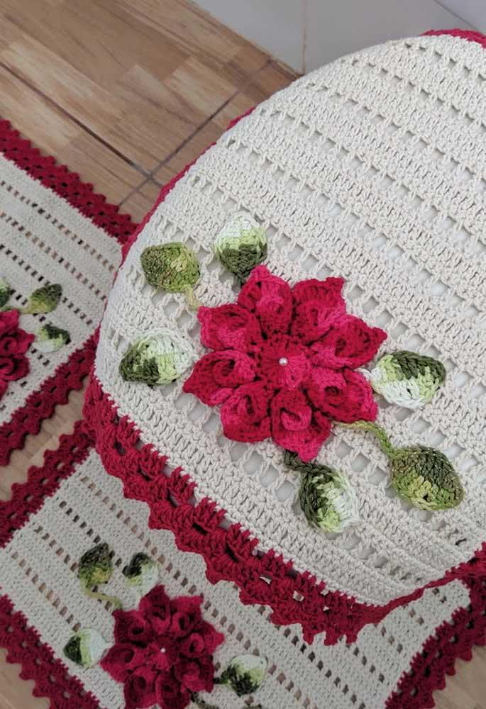 Jogo de banheiro branco de crochê com bordas vermelhas e rosa com folhas.
