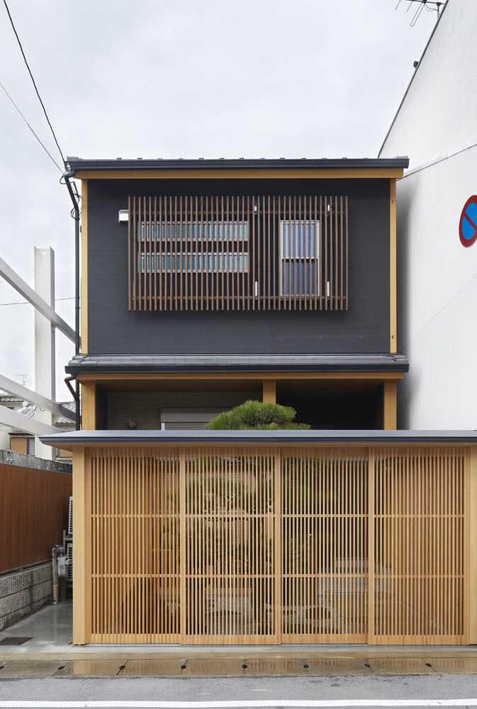 Já aqui, os painéis ripados de madeira trazem acolhimento para fachada da casa japonesa