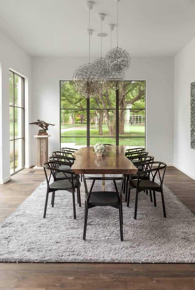 Mesa de madeira rústica combinada a cadeiras modernas