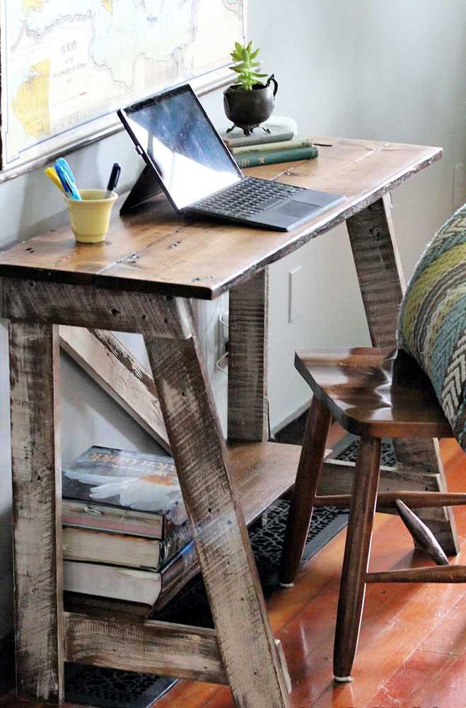 A bancada de trabalho ganhou uma mesa de madeira rústica com acabamento em patiná